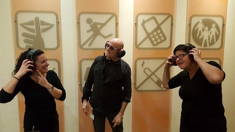 שלושה מדריכים בתערוכה עם אוזניות