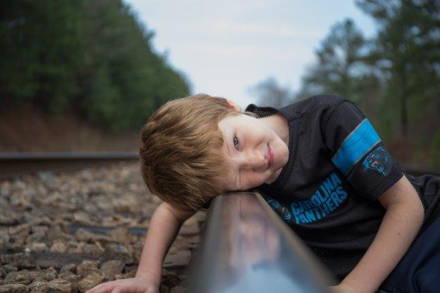 ילד מניח ראש על מעקה ברזל ומקשיב