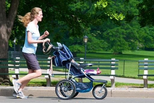 אמא רצה בפארק עם התינוק בעגלה