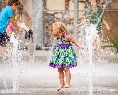 ילדה עם שמלה צבעונית משחק במזרקת מים