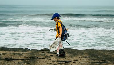 ילד בחוף הים אוסף אשפה