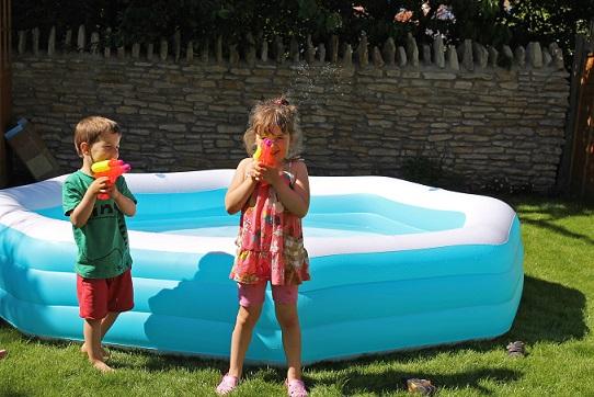 ילד וילדה בבריכת מים עם רובי מים