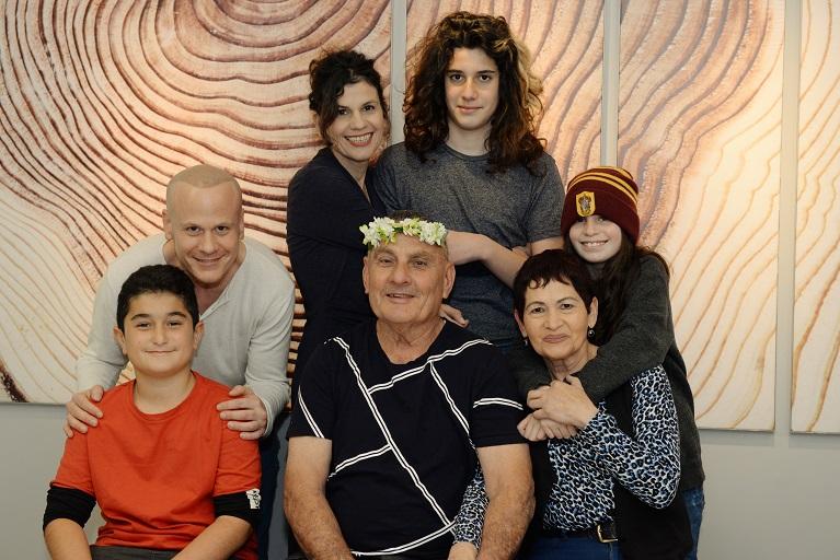 סבא עם זר יומולדת על ראשו וסביבו בני משפחתו