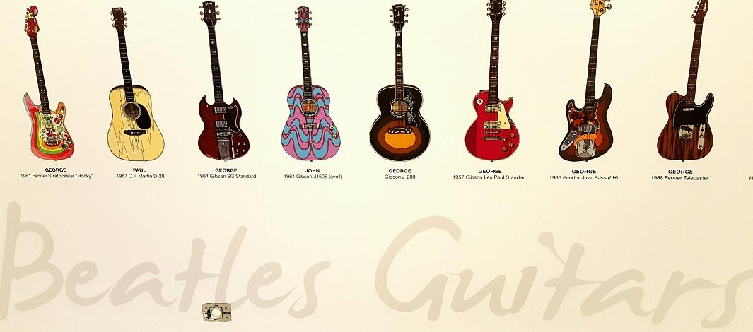 איור של הגיטרות של הביטלס בתערוכה במוזיאון