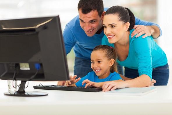 ילדה יושבת מול מחשב והורים עומדים מאחוריה.