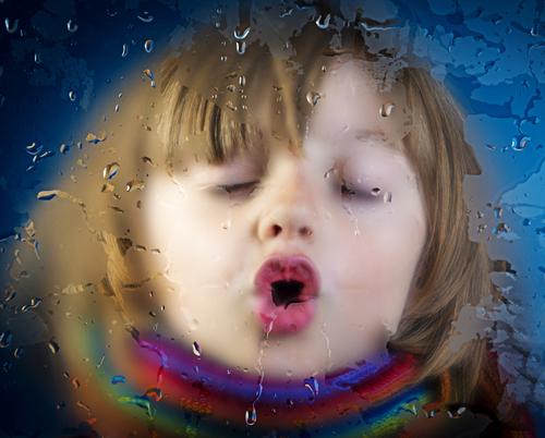 ילדה מצמידה את פניה לחלון כשבחוץ יורד גשם