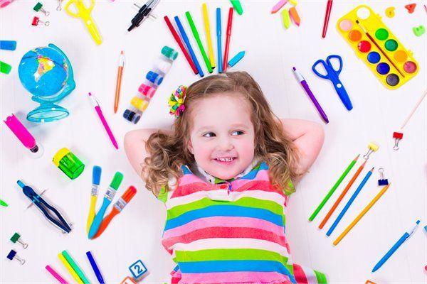 ילדה מחייכת כשהיא מוקפת בשלל כלי כתיבה צבעוניים
