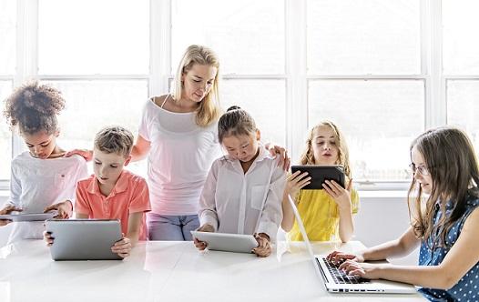 חמישה ילדים עם מחשבים ואישה איתם.
